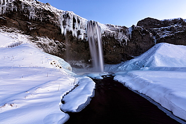 Winter view of Seljalandsfoss Waterfall at dusk with snow covered foreground and icicles hanging from cliffs, South Iceland, Polar Regions