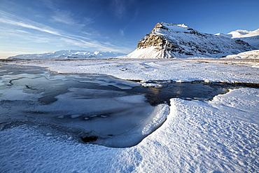 Snow covered landscape in winter with frozen pool, mountain and Vatnajokull Glacier, near Jokulsarlon Lagoon, South Iceland, Polar Regions