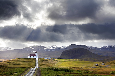 Ingjaldsholskirkja set against mountains on a dramatic stormy day, near Rif, Snaefellsnes Peninsula, Iceland, Polar Regions