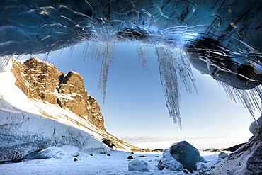 View from ice cave towards sunlit mountains with icicles hanging from cave entrance, near Jokulsarlon, South Icelan, Polar Regions