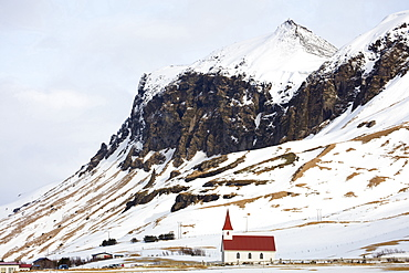 Red and white church against snow covered mountains, Vik, South Iceland, Polar Regions