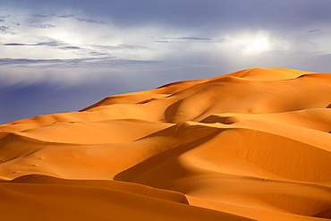 Orange sand dunes against stormy sky, Erg Chebbi sand sea, part of the Sahara Desert near Merzouga, Morocco, North Africa, Africa