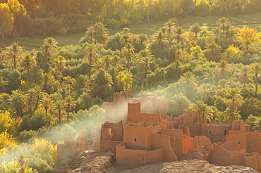 Ruined kasbah in the palmerie near Tinerhir, with smoke from fire swirling through the palm trees, Morocco, North Africa, Africa