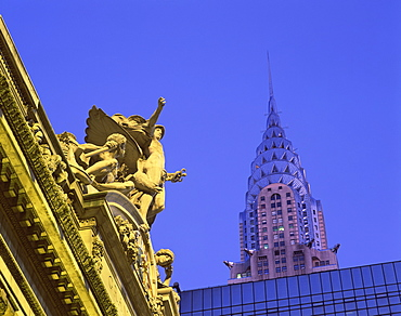 Close-up of statues on top of Grand Central Station, with the Chrysler Building in the background, taken in the evening in New York, United States of America, North America