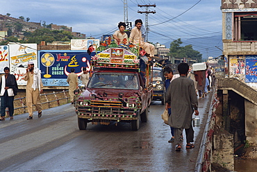 Men riding on the roof of a pick-up taxi in the main street of Mingora in the Swat valley, Pakistan, Asia