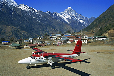 Small propellor aeroplane on the airstrip at Lukla, with village and mountains in the background, in the Himalayas, Nepal, Asia