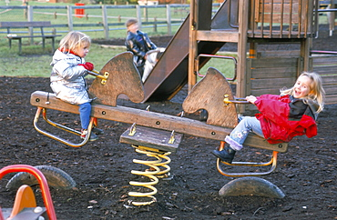 Fair haired sisters playing on a seesaw
