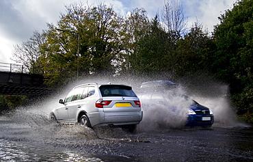 Vehicles splash through flood water on public road, London, England, United Kingdom, Europe
