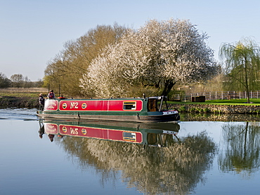 Spring blossom and red narrow boat reflected in tranquil River Thames, Oxfordshire, England, United Kingdom, Europe
