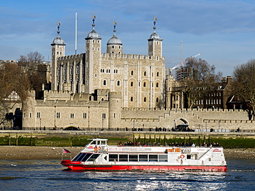 Tower of London, UNESCO World Heritage Site across the River Thames with tour boat, London, England, United Kingdom, Europe