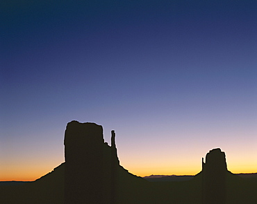 Silhouettes of mitten rock formations at sunset, Utah, United States of America (USA), North America