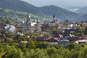 Town nestled in valley in foothills of Carpathian Mountains where churches are the dominant buildings in the village, Varma, Transylvania, Romania, Europe