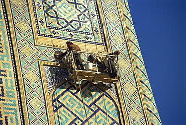 Workers in cradle refurbishing the 17th century Sher Dor Madressa, Registan Square, Samarkand, Uzbekistan, Central Asia, Asia