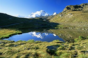The Breithorn reflected in lake, white chapel in distance on hillside, Zermatt, Valais, Switzerland, Europe