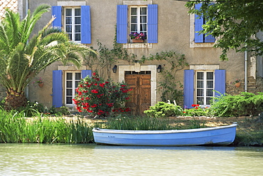 Boat moored alongside house on the bank of the Canal du Midi, Le Somail, Aude, Languedoc Roussillon, France, Europe