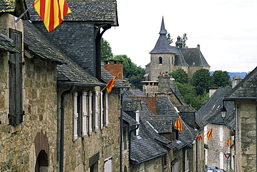 View along village street to church, with colourful flags, Turenne, Correze, Limousin, France, Europe