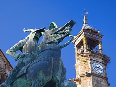 Equestrian statue of Francisco Pizarro in the Plaza Mayor, clock-tower of the Iglesia de San Martin beyond, Trujillo, Caceres, Extremadura, Spain, Europe