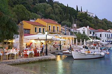 Typical waterfront taverna illuminated at dusk, Kioni, Ithaca (Ithaki), Ionian Islands, Greek Islands, Greece, Europe