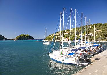 View across Lakka Bay, yachts lined up along the quay, Lakka, Paxos, Paxi, Corfu, Ionian Islands, Greek Islands, Greece, Europe