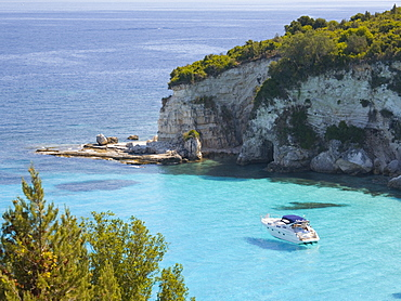 View from hillside over secluded Voutoumi Bay, solitary boat at anchor, Antipaxos, Paxi, Corfu, Ionian Islands, Greek Islands, Greece, Europe