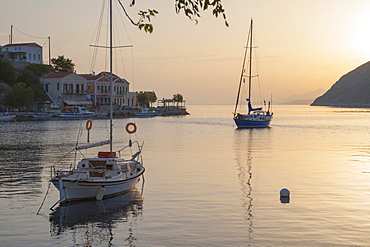 View across the tranquil harbour, sunrise, Gialos (Yialos), Symi (Simi), Rhodes, Dodecanese Islands, South Aegean, Greece, Europe
