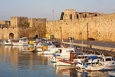 View across tranquil Kolona Harbour to the city walls, sunrise, Rhodes Town, Rhodes, Dodecanese Islands, South Aegean, Greece, Europe
