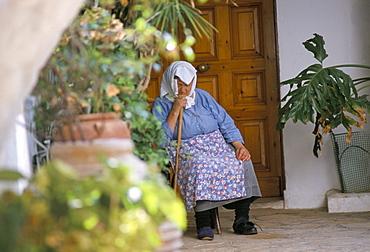 Old woman dozing at monastery, Paleokastritsa, Corfu, Greek Islands, Greece, Europe