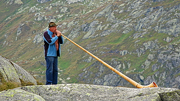 Alpenhorn player at Gotthard Pass, Canton of Uri, Switzerland, Europe