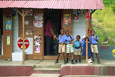Portrait of schoolchildren waiting for bus outside a shop, near Roxborough, Tobago, West Indies, Caribbean, Central America