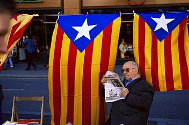 Reading the newspaper under the Catalan flag on La Rambla, Barcelona, Catalonia, Spain, Europe