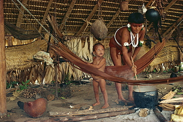 Yanomami Indian woman cooking, stirring pot, with infant nearby, Brazil, South America