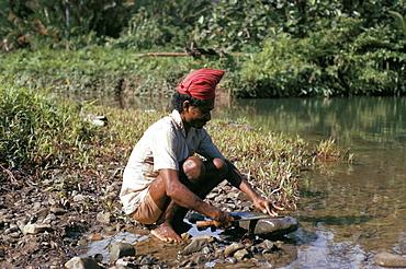 Hua Ulu man sharpening knife, Seram, Moluccas, Indonesia, Southeast Asia, Asia