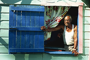 Portrait of elderly man at window of house, Gales Point, Belize, Central America