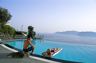 Holidaymakers on lilos in pool and view across bay, Oia, Santorini (Thira), Greek Islands, Greece, Europe