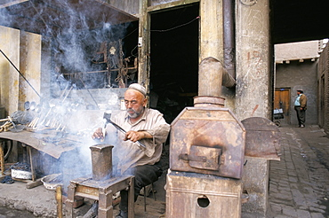 Blacksmith at work, Sunday market, Kashi, Xinjiang, China, Asia