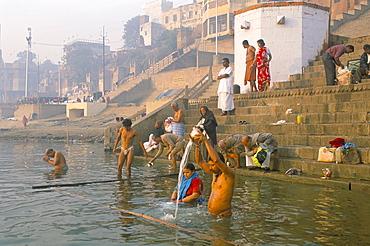 Men and women washing in the River Ganges at Scindia Ghat, Varanasi (Benares), Uttar Pradesh, India, Asia