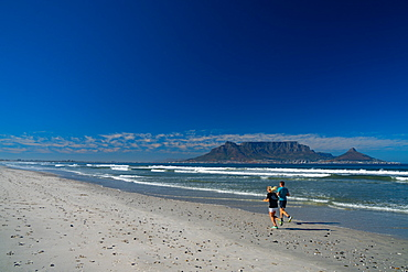 Joggers running on Blouberg Beach in the early morning, with Table Mountain in the background, Cape Town, South Africa, Africa