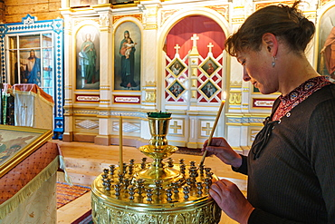 Local woman cleaning the candle holder at Obinitsa Orthodox Church, built 1952, SE Estonia, Europe