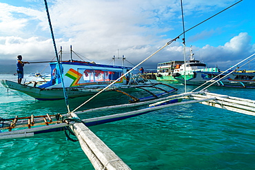 Bangkas (outrigger canoes) and the old ferry compete for landing space at the harbour, Borocay Island, Philippines, Southeast Asia, Asia