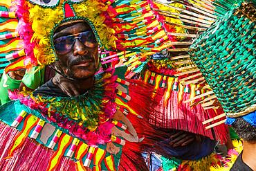 Cool participant in dark glasses and flamboyant coloured dress at the annual Ati-Atihan Festival, Kalibo Island, Philippines, Southeast Asia, Asia