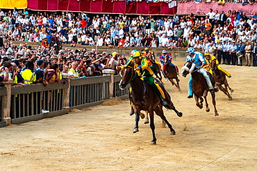 Jockeys in colourful outfits representing their respective neighbourhoods at full pelt at the Palio, a bareback horserace, Siena, Tuscany, Italy, Europe