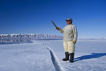 Inuit hunter line fishing at the floe edge for Arctic cod, sculpin and halibut near Herbert Island, Greenland, Denmark, Polar Regions