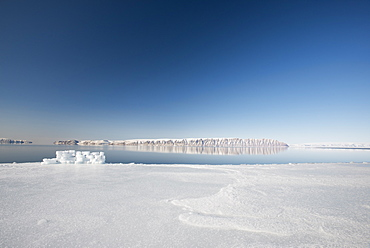 Hunting blind made from ice blocks at the Floe edge, the junction of sea ice and the ocean, Herbert Island in the background, Greenland, Denmark, Polar Regions - 465-3412