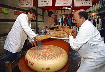 Two foot diameter Gruyere cheese being cut to size in market, Luxembourg City, Luxembourg, Europe