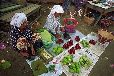 Women selling local produce including star fruit, plums and beeswax at Kota Belud weekly Tamu or market in Sabah, Malaysia, Borneo, Southeast Asia, Asia