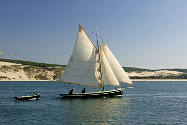Od gaff rigged sailing yacht and dinghy, sailing along Dune du Pyla, Bay of Arcachon, Gironde, Aquitaine, France, Europe
