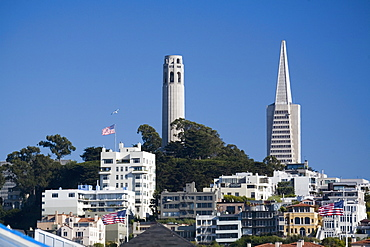 Coit Tower and Transamerica Pyramid, with apartment blocks and three US flags, San Francisco, California, United States of America, North America