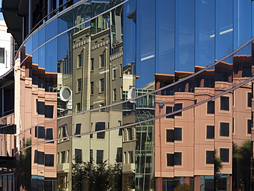 City council buildings in Civic Square reflecting in glass wall of public library, Wellington, North Island, New Zealand, Pacific