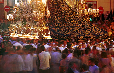 Malaga-Spain - Easter Week (Semana Santa) - Crowds mill around the giant cloak of the Virgen de la Trinidad as her float passes through the city streets