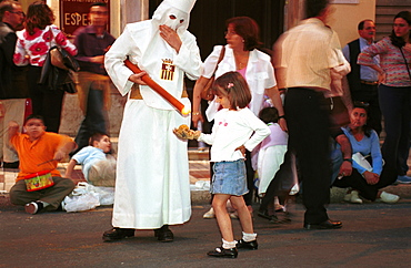 Malaga-Spain - Easter Week (Semana Santa) - A girl collects candle wax from a penitent during a procession